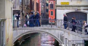Gente que cruza el puente sobre el canal del agua adentro metrajes
