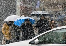 Gente que cruza la calle nevosa de la ciudad en nevadas pesadas y un coche de conducción delante de ellos foto de archivo