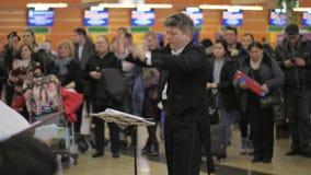 Gente que da aplauso al coro que se realiza en el aeropuerto de Sheremetyevo, Moscú almacen de video