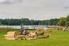 Gente que descansa por un lago Imagen de archivo libre de regalías
