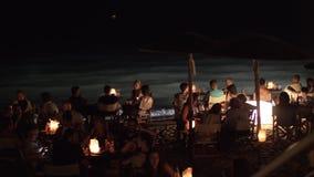 Gente que disfruta de la igualación en café de la playa en la orilla almacen de metraje de vídeo