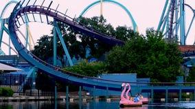 Gente que disfruta de paseo en los barcos del cisne de la paleta en el lago azul en fondo del roller coaster del Mako en el parqu metrajes