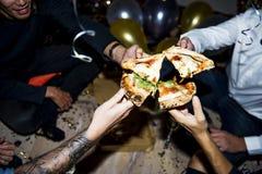 Gente que disfruta de un partido de la pizza Fotos de archivo