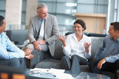 Gente que disfruta de una charla ocasional en el salón de la oficina