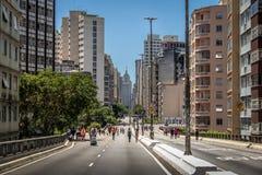 Gente que disfruta del fin de semana en la carretera elevada Minhocao con el edificio viejo de Banespa en fondo - Sao Paulo, el B imagen de archivo