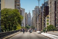 Gente que disfruta del fin de semana en la carretera elevada Minhocao con el edificio viejo de Banespa en fondo - Sao Paulo, el B foto de archivo