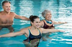 Gente que ejercita en piscina Imágenes de archivo libres de regalías