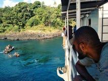 gente que espera en un barco de carga al lado de una isla tropical imponente mientras que carga con una canoa de soporte local fotos de archivo libres de regalías