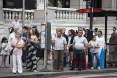 Gente que espera en una parada de autobús fotos de archivo
