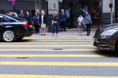 Gente que espera para cruzar la calle, paso de peatones en el camino ocupado, tráfico diario de la ciudad fotografía de archivo