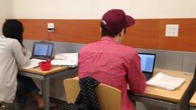 Gente que estudia en la biblioteca almacen de metraje de vídeo