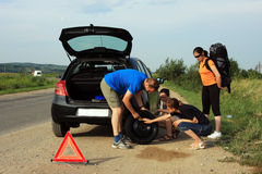 Gente que fija un neumático plano Foto de archivo libre de regalías