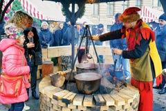 Gente que goza de la comida tradicional en el mercado de la Navidad de Riga Imagen de archivo libre de regalías