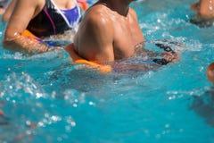 Gente que hace aeróbicos de agua en una piscina al aire libre Imagen de archivo