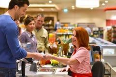 Gente que hace compras para la comida en el supermercado - el pagar del pago y envío imagen de archivo libre de regalías