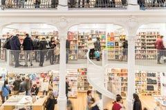 Gente que hace compras para los libros en biblioteca Foto de archivo