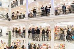 Gente que hace compras para los libros en biblioteca Imagen de archivo libre de regalías