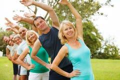 Gente que hace ejercicios de la flexibilidad. Foco en primero plano. Fotografía de archivo libre de regalías