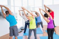 Gente que hace estirando ejercicio en clase de la yoga Fotos de archivo