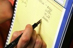 Gente que hace la lista, mano que sostiene la pluma Foto de archivo