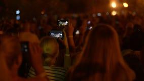 Gente que hace los vídeos en sus smartphones con el fuego artificial después de festival de música almacen de metraje de vídeo