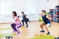 Gente que hace posiciones en cuclillas con los barbells en los hombros que ejercitan en el club de fitness fotos de archivo