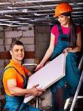Gente que instala el techo suspendido imagenes de archivo