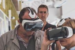 Gente que intenta las auriculares 3D en la expo 2015 en Milán, Italia Imagen de archivo