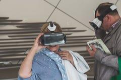 Gente que intenta las auriculares 3D en la expo 2015 en Milán, Italia Imagenes de archivo