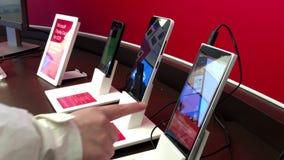 Gente que juega el nuevo teléfono elegante en la tienda de Microsoft almacen de metraje de vídeo