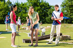 Gente que juega a golf miniatura al aire libre Fotografía de archivo libre de regalías