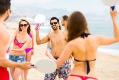 Gente que juega a juegos activos en la playa imagenes de archivo