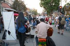 Gente que juega la música para la caridad del dinero en la calle que camina de domingo Fotografía de archivo libre de regalías