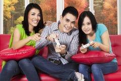 Gente que juega la videoconsola en casa Foto de archivo libre de regalías