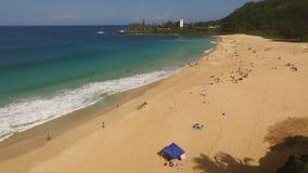 Gente que juega las ondas que practican surf que estrellan el Océano Pacífico Oahu de la orilla del norte almacen de video