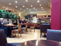 Gente que lee y que se relaja en un restaurante Imagen de archivo