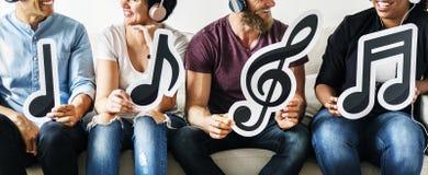 Gente que lleva a cabo iconos de la nota musical Foto de archivo