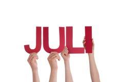 Gente que lleva a cabo la palabra alemana recta Juli Mean July Foto de archivo libre de regalías