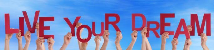 Gente que lleva a cabo la palabra roja Live Your Dream Blue Sky Foto de archivo libre de regalías