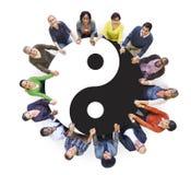 Gente que lleva a cabo las manos con Yin Yang Symbol Imágenes de archivo libres de regalías