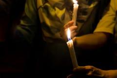 Gente que lleva a cabo vigilia de la vela en la esperanza que busca de la oscuridad, adoración Imagen de archivo libre de regalías