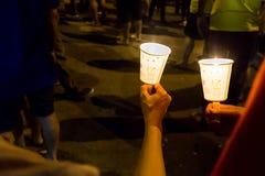 Gente que lleva a cabo vigilia de la vela en la esperanza que busca de la oscuridad, adoración Imagenes de archivo