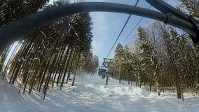 Gente que lleva de la telesilla de la montaña a esquiar pista, resto activo del invierno, turismo metrajes