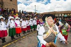 Gente que lleva la ropa tradicional y máscaras que bailan el Huaylia en el día de la Navidad delante de la catedral de Cuzco en C Fotos de archivo libres de regalías