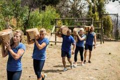 Gente que lleva registros de madera pesados durante carrera de obstáculos Foto de archivo