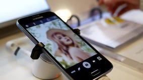 Gente que mira el precio con el teléfono móvil de la nota 7 de la galaxia de Samsung de la exhibición almacen de metraje de vídeo