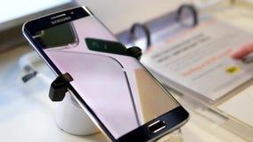 Gente que mira el precio con el teléfono móvil de la nota 7 de la galaxia de Samsung de la exhibición almacen de video