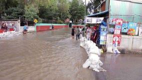Gente que mira el río creado en las calles debidas la inundación