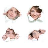 Gente que mira furtivamente a través del agujero en papel Imagenes de archivo
