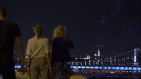 Gente que mira y que hace photoes de fuegos artificiales sobre el puente vídeo 4K almacen de video